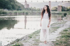 Beautiful young woman with long curly hair dressed in boho style dress posing near lake Stock Images