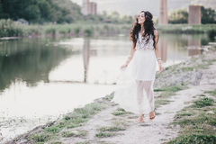 Beautiful young woman with long curly hair dressed in boho style dress posing near lake. Summer mood Royalty Free Stock Image