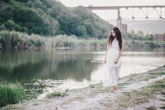 Beautiful young woman with long curly hair dressed in boho style dress posing near lake stock image