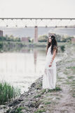 Beautiful young woman with long curly hair dressed in boho style dress posing near lake royalty free stock photography