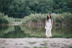 Beautiful young woman with long curly hair dressed in boho style dress posing near lake. Summer mood stock images