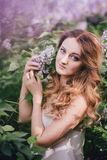 Beautiful young woman with long curly hair in a garden with lilacs Stock Image