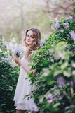 Beautiful young woman with long curly hair in a garden with lilacs Stock Photo