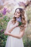 Beautiful young woman with long curly hair in a garden with lilacs Royalty Free Stock Images