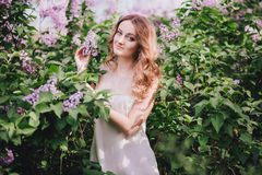 Beautiful young woman with long curly hair in a garden with lilacs Royalty Free Stock Photo