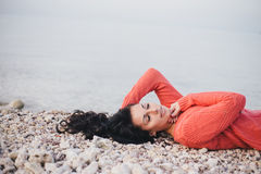 Beautiful young woman with long curly hair lying on the beach Stock Photography