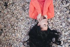 Beautiful young woman with long curly hair lying on the beach Stock Photo