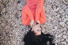 Beautiful young woman with long curly hair lying on the beach Stock Image