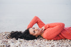 Beautiful young woman with long curly hair lying on the beach Royalty Free Stock Image