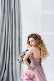 Beautiful young woman with long curly hair in a pink dress. Stock Images