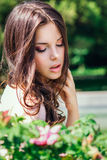 Beautiful young woman with long curly hair posing near roses in a garden. The concept of perfume advertising. Stock Photos