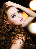 Beautiful young woman with long curly hairs. Portrait of a beautiful young woman with long curly hairs over bright night lights royalty free stock photo