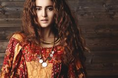 Beautiful young woman with long curly hairstyle, fashion jewelry with brunette hair. Indian style clothes, long dress stock images