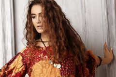 Beautiful young woman with long curly hairstyle, fashion jewelry with brunette hair. Indian style clothes, long dress Royalty Free Stock Images