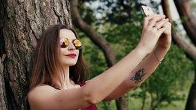 Beautiful young woman with long dark hair in sunglasses taking selfie, at the park at sunset. slow mo stock video