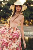 Beautiful young woman with long dark hair wears elegant dress and hat Stock Photo