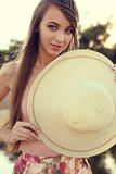 Beautiful young woman with long dark hair wears elegant dress and hat Royalty Free Stock Image