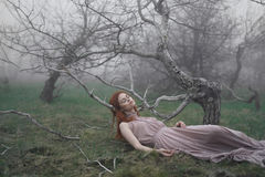Beautiful young woman in a long dress lies in the grass, fog Royalty Free Stock Photos