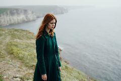 Beautiful young woman in a long green coat on the edge of a mountain cliff near the sea.  royalty free stock images