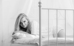 Beautiful young woman with long hair on bed. Royalty Free Stock Photo
