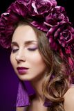 Beautiful girl with purple makeup and flowers. Beautiful young woman with long hair and purple makeup. Flower wreath on head. Studio beauty shot on dark royalty free stock photos