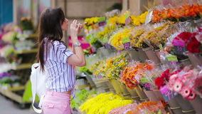 Beautiful young woman with long hair selecting fresh flowers at european market stock video