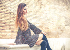 Beautiful young woman with long hair sitting on a marble bench. Outdoors with brick wall in the background. Youth fashion Royalty Free Stock Image