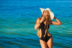Beautiful young woman with long hair in a straw hat sea in the b. Ackground stock images