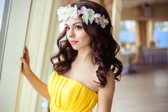 Beautiful young woman with long hair in a summer day. bridesmaid in yellow dress in a sea restaurant. Fashion beauty portrait Royalty Free Stock Images