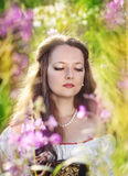 Beautiful young woman with long hair on summer meadow Stock Photos