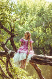 Beautiful young woman with long hair, twisted into a braid, in  pink dress sitting on  lush tree. Beautiful young woman with long hair, twisted into a braid, in Stock Photography
