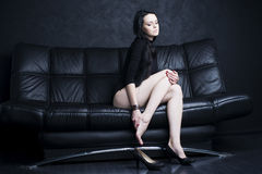 Beautiful young woman with long legs in bodysuit. Leg pain Stock Images