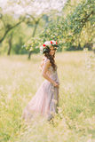 Beautiful young woman in long lilac dress with wreath on head standing back outdoors Stock Image