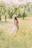 Beautiful young woman in long lilac dress with wreath on head standing back outdoors Royalty Free Stock Image