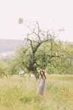 Beautiful young woman in long  lilac  dress with wreath on head standing near tree Stock Photo