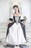 Beautiful young woman in long medieval dress making curtsey Stock Image