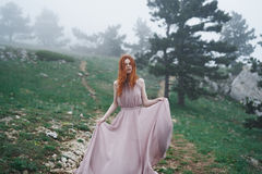 Beautiful young woman in a long pink dress in the mountains Royalty Free Stock Image