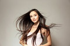 Beautiful young woman with long straight hair. On light background Stock Images