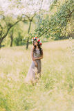 Beautiful young woman in long violet dress with wreath of red and white flowers on head standing looking towards outdoors Royalty Free Stock Photos