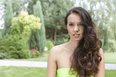 Beautiful young woman with long wavy hair in park Stock Photo