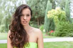 Beautiful young woman with long wavy hair in park stock photos
