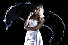 Beautiful young woman in a long white dress and with black wings Royalty Free Stock Images