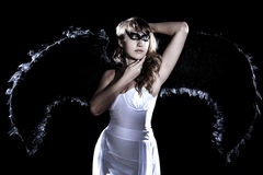 Beautiful young woman in a long white dress and with black wings Stock Photo