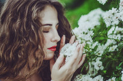 Beautiful young woman in a long white dress with long wavy hair,. Lying on the large roots of a tree with eyes closed. Fairy tale. Dream Stock Photo