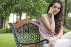 Beautiful young woman looking away while on call in park Stock Photos