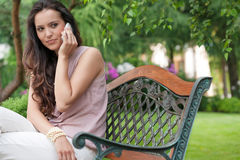 Beautiful young woman looking away while on call in park Royalty Free Stock Images