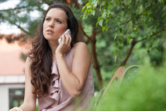 Beautiful young woman looking away while on call at park Stock Photo