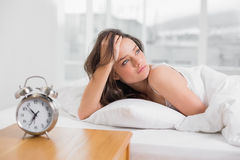 Beautiful young woman looking away while lying in bed Stock Photo