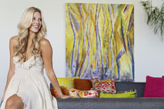 Beautiful young woman looking away with painting in background Stock Photography