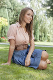 Beautiful young woman looking away while relaxing on grass in park Royalty Free Stock Photo
